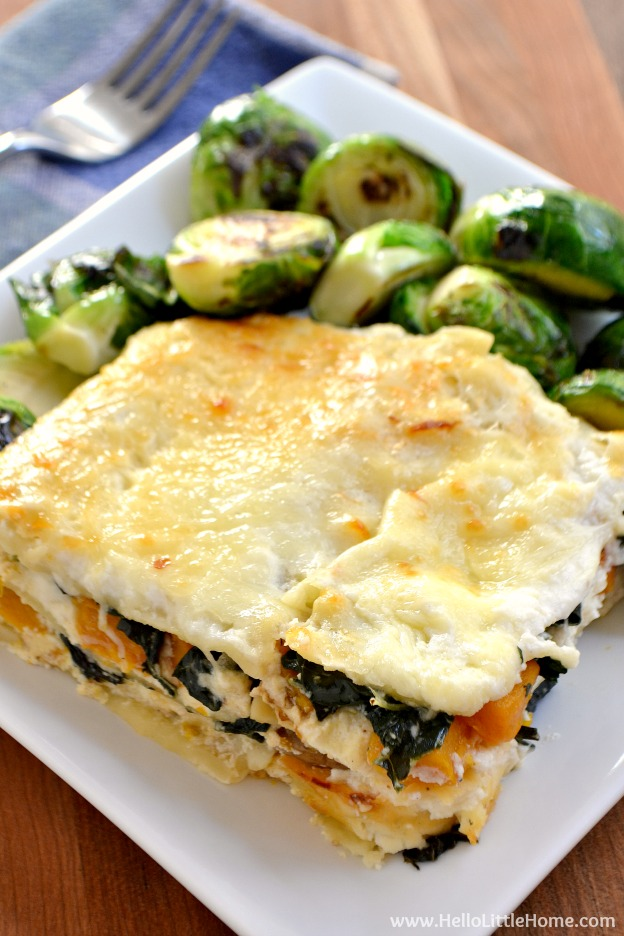 A piece of Butternut Squash Lasagna served with brussels sprouts on a white plate.