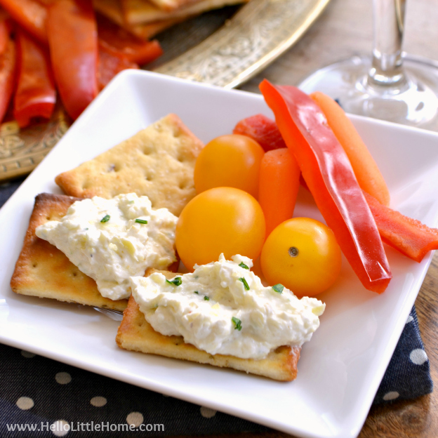 A plate with crackers, veggies, and creamy lemon artichoke spread.