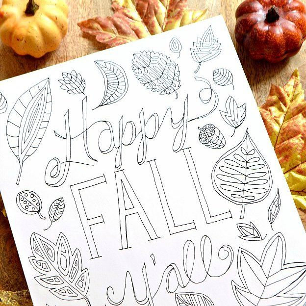 A fall coloring page decorated with leaves on a wood table.