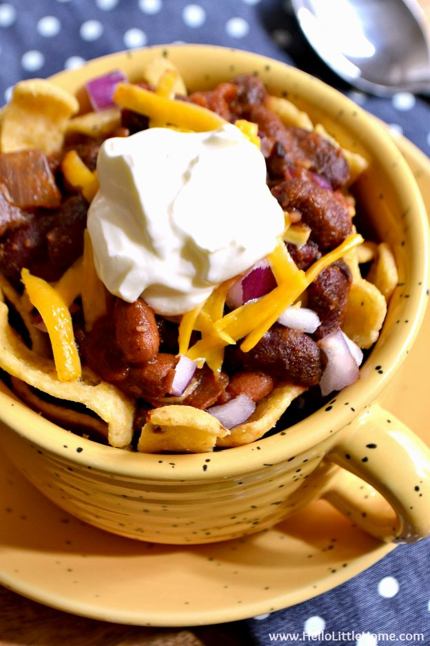 Vegetarian Frito Pie in a yellow mug and a spoon on a polka dot napkin.