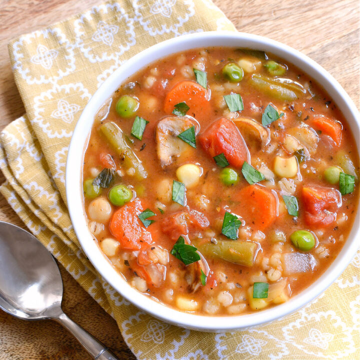 A bowl of Vegetable Barley Soup on a yellow napkin next to a spoon.