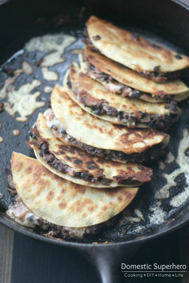 A skillet filled with crispy black bean tacos.