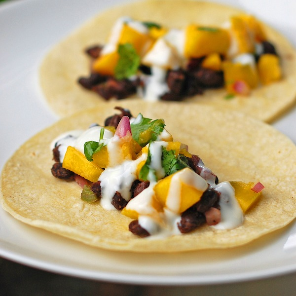 25 Vegetarian Tacos Recipes that are perfect for Taco Tuesday or any night of the week, like these Mango Black Bean Tacos from Pinch of Yum! These healthy taco recipes are a great easy dinner idea. Lots of tasty vegan taco options, too! | Hello LIttle Home