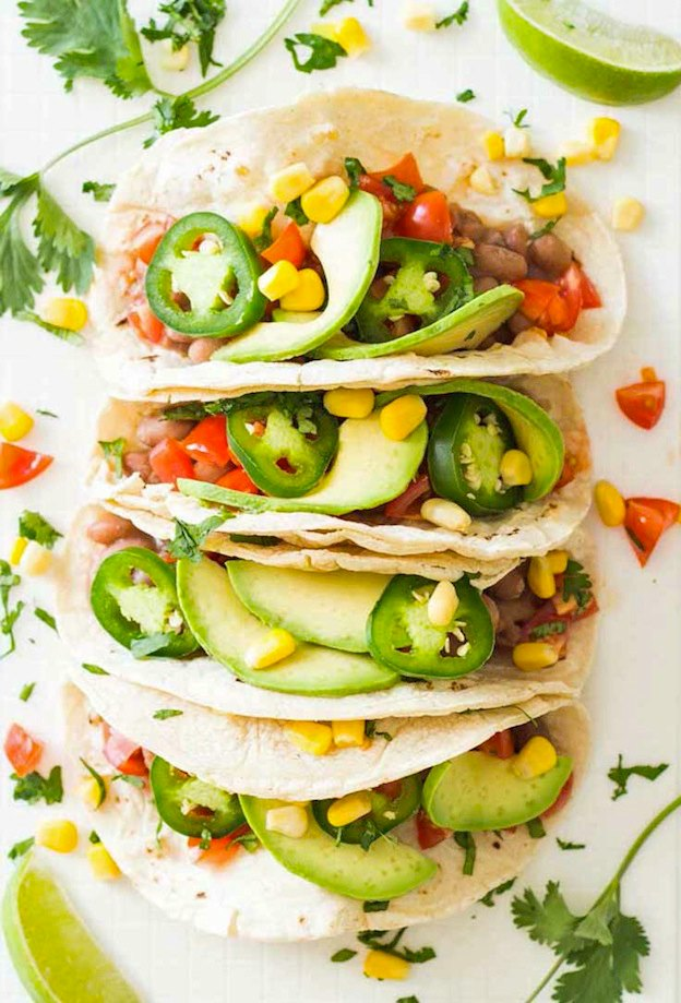Tortillas arranged in a row and filled with pinto beans, avocado, and jalapenos.