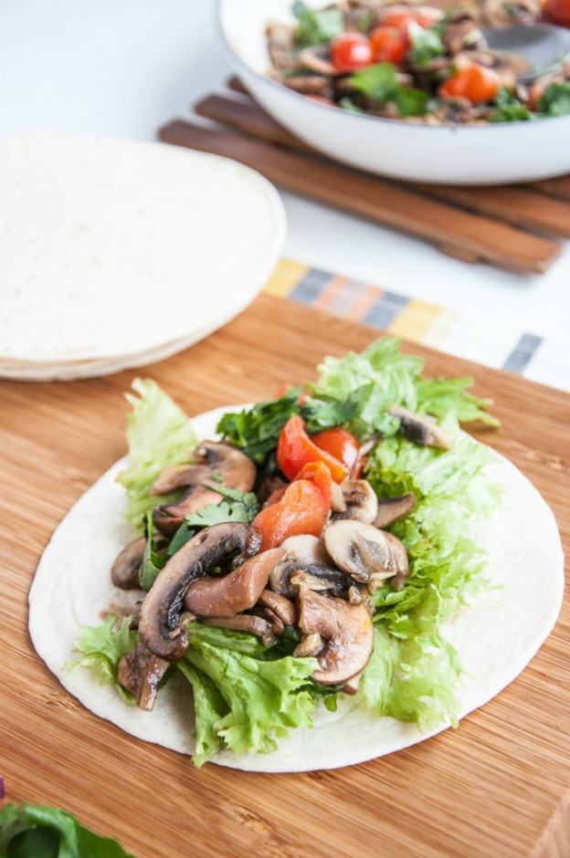 Mushrooms, lettuce, and tomatoes served on a tortilla.