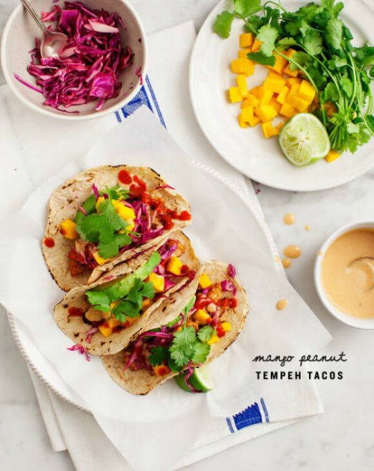 Tacos made with tempeh and mango serve on a white plate.