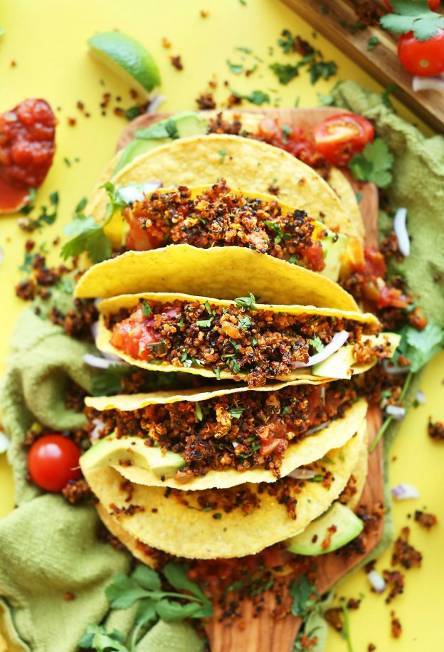 Crispy tacos with a quinoa filling arranged on a yellow background.