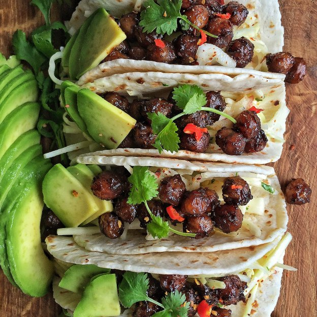 Tacos filled with crispy chickpeas and served with avocado slices.