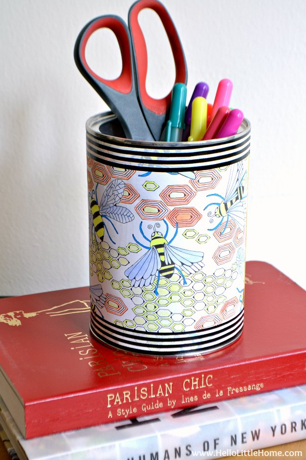 A storage container for pens wrapped in a finished coloring page.