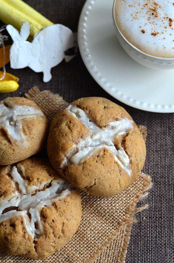 Three buns on a burlap napkin next to a coffee cup.