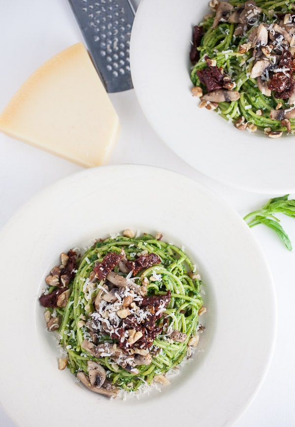 Two bowls of pesto pasta and a wedge of parmesan cheese on a table.