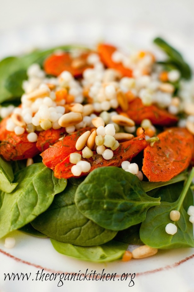 A spinach salad topped with carrots.
