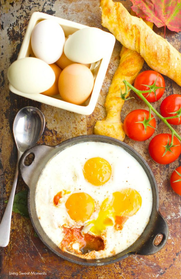 A dish of baked eggs on a tray topped with bread sticks, fresh tomatoes, and more eggs.