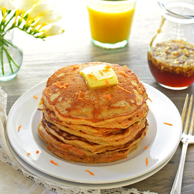 A stack of pancakes topped with butter.