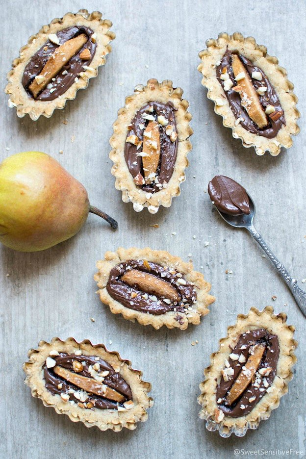 Mini tarts and a pear on a wood table.
