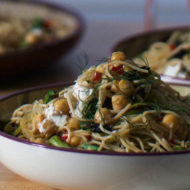 A white bowl heaped full of pasta with chickpeas and fresh herbs.