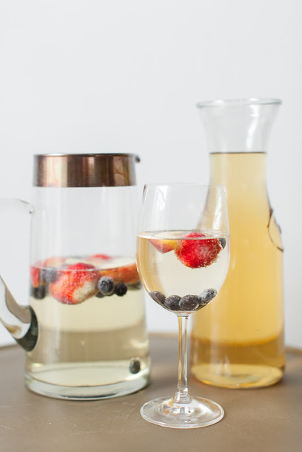 Two pitchers and a wine glass filled with a cocktail on a table.