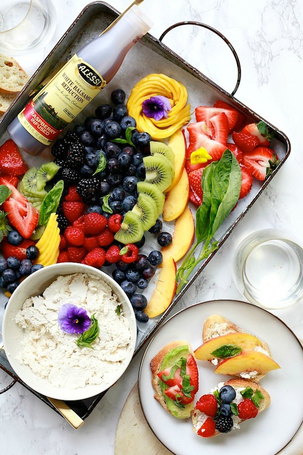 A tray topped with fresh fruit and a spread.