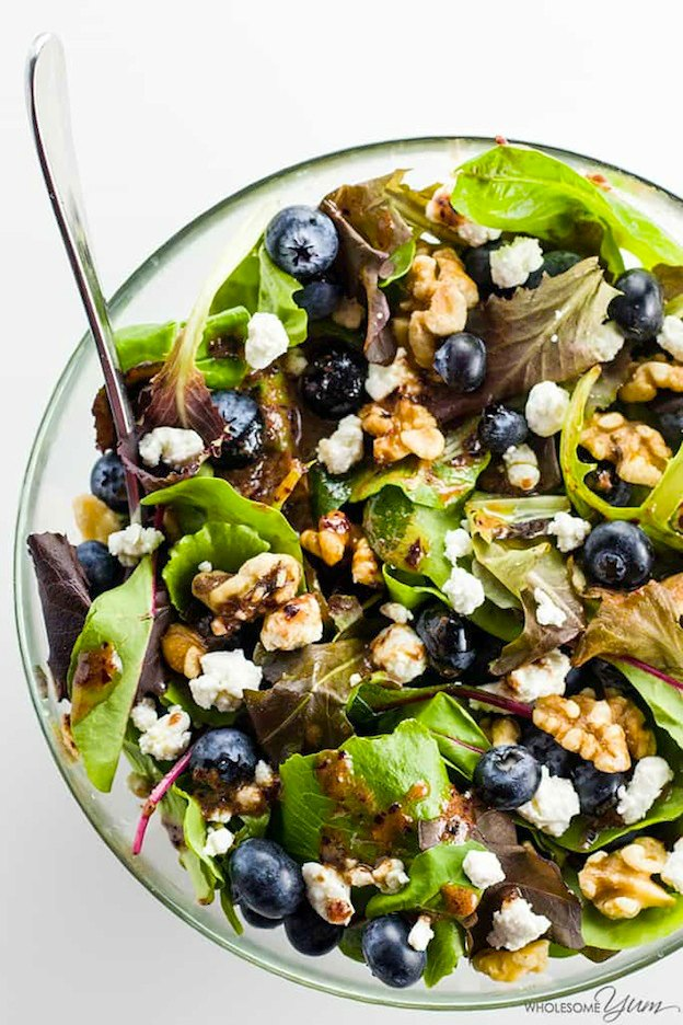 A salad topped with blueberries, nuts, and cheese served in a glass bowl.