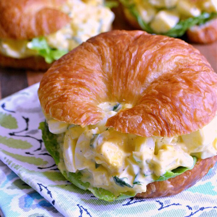 A deviled egg salad sandwich on a blue patterned napkin.