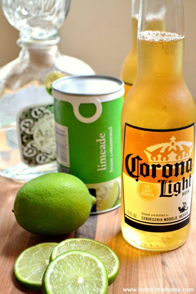 Beergarita ingredients arranged on a wood table.