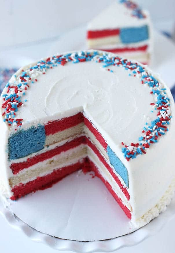 A layer cake with a flag pattern inside on a white platter.
