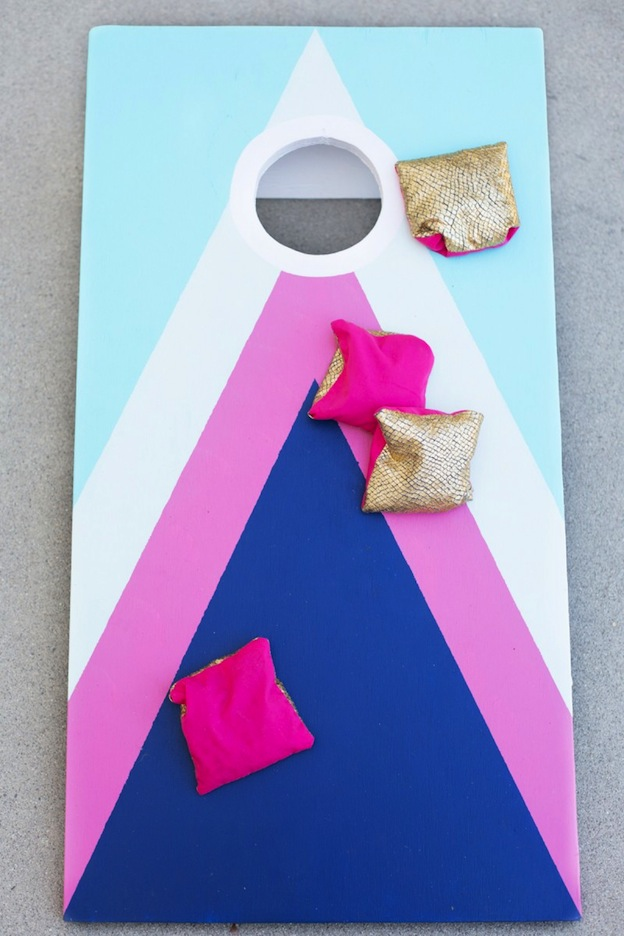 20+ DIY Yard Games that are perfect for summer entertaining, like this DIY Cornhole Game from Lovely Indeed! These awesome lawn games for adults and kids - like cornhole, giant Jenga, Yardzee, tic tac toe + more - are perfect for backyards, camping trips, and family fun. Learn how to make DIY yard games from these easy tutorials, then enjoy these game all summer long! | Hello Little Home