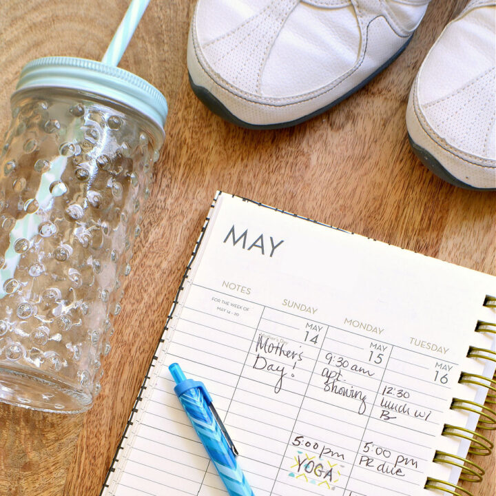 A water bottle, sneakers, and planner on a wood table.
