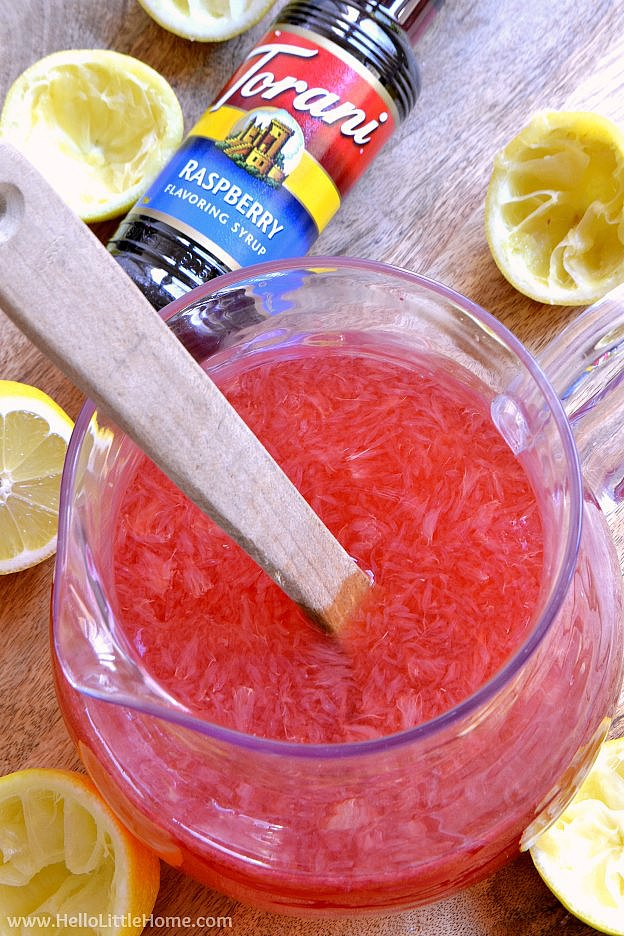 Mixing together the ingredients for Spiked Lemonade in a pitcher.