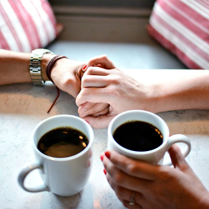 A couple holding hands while drinking coffee.