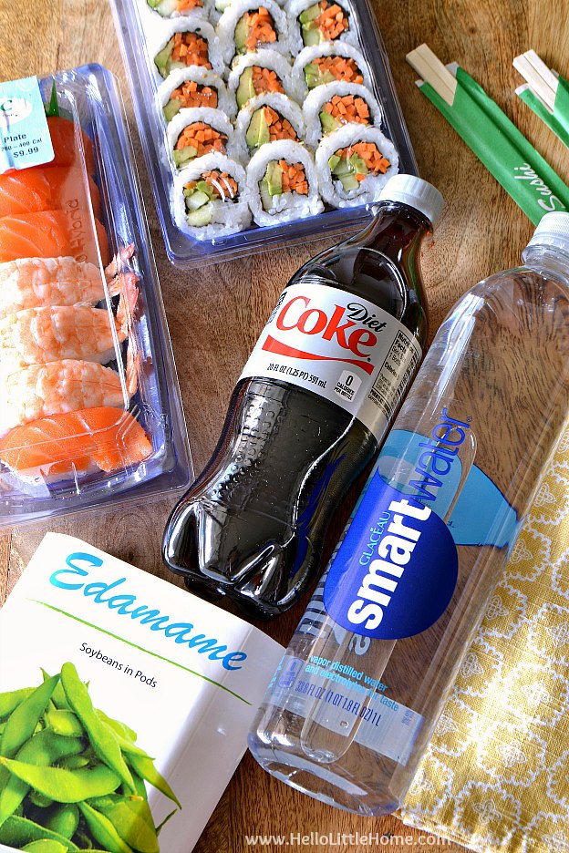 Package of sushi, edamame, and drinks on a wood table.