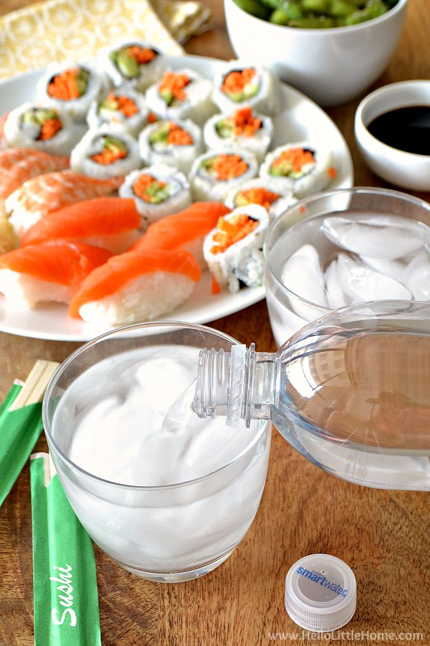 Pour glasses of water with a plate of sushi in the background.