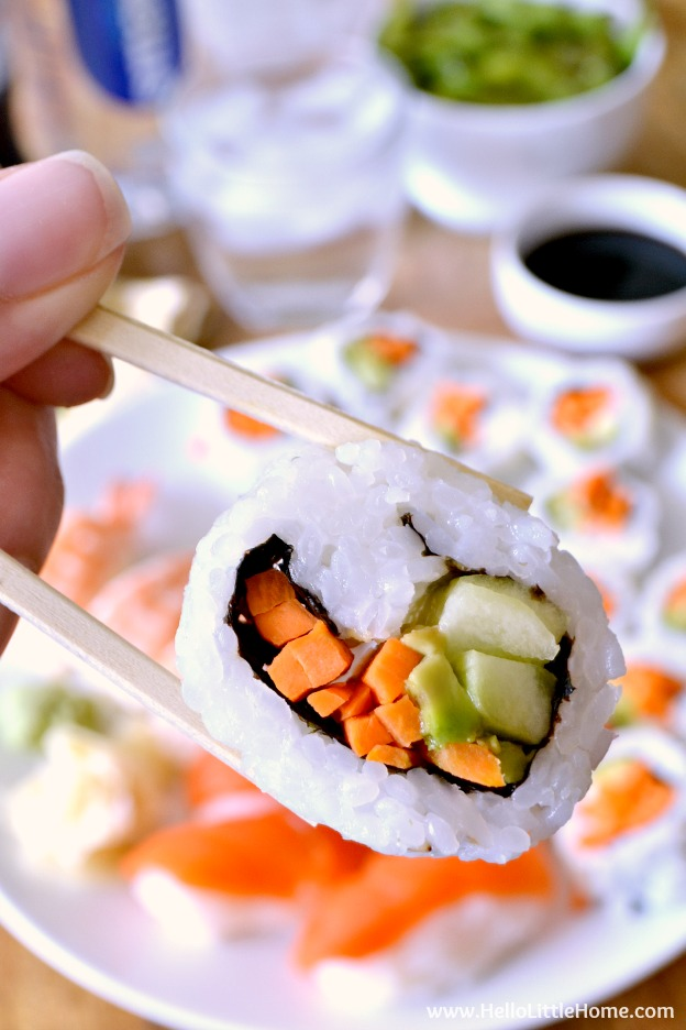 A closeup of a piece of sushi held by a pair of chopsticks.