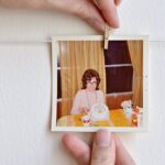 Adding photographs to a DIY photo display with clothespins. | Hello Little Home