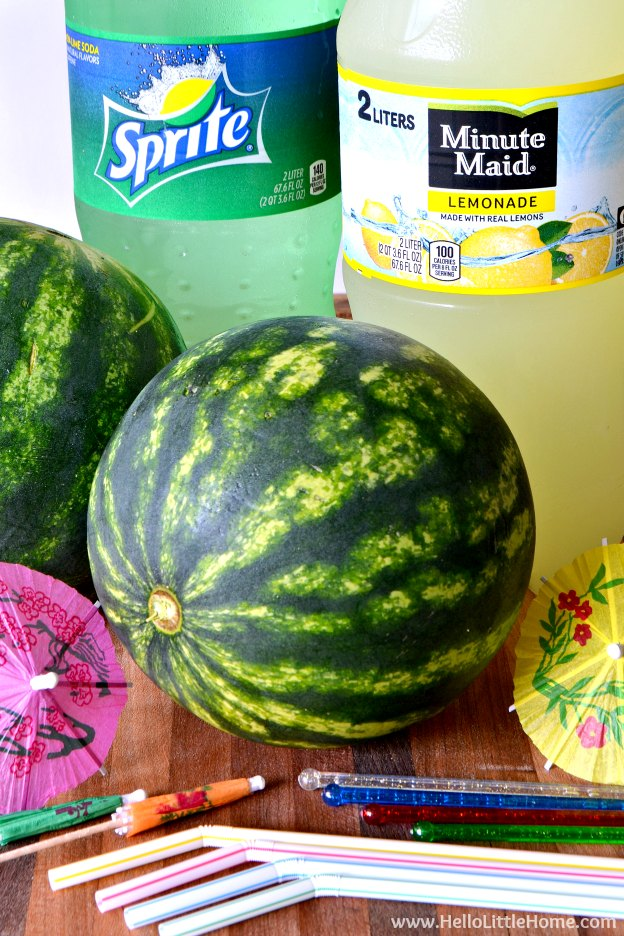 Watermelon Punch ingredients (lemonade, Sprite, mini watermelons, and garnishes) on a wood board.