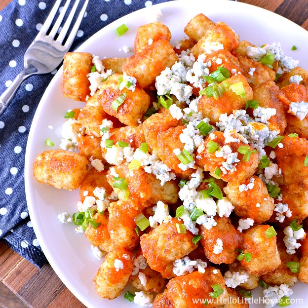 Easy Buffalo Tatchos (Tater Tot Nachos) ... a fun and easy game day recipe! These easy vegetarian tater tot nachos are loaded with a spicy homemade buffalo sauce, creamy blue cheese, and fresh green onions. Makes a great appetizer for game day parties or a yummy snack any day! | Hello Little Home
