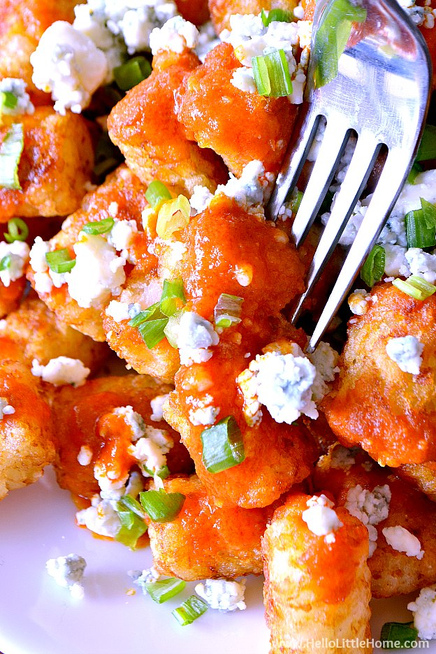 A fork spearing a tater tot topped with buffalo sauce and blue cheese.