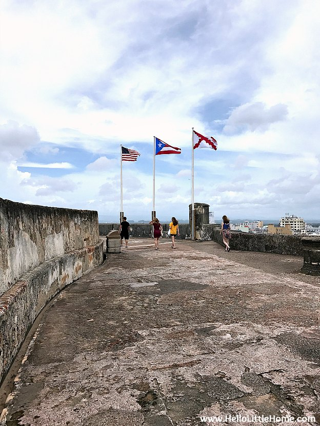 U.S., Puerto Rico, and Cross of Burgundy (a Spanish military flag) flags atop Castillo San Cristóbal, part of the San Juan National Historic Site and one of the best things to do in San Juan, Puerto Rico! | Hello Little Home