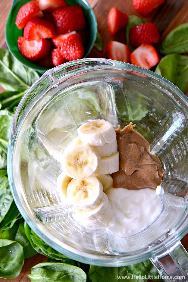 Strawberry Banana Green Smoothie recipe! Learn how to make this delicious, simple green smoothie recipe that's packed with protein and nutritious ingredients, like yogurt, almond butter, spinach, and fresh fruit! This strawberry banana smoothie makes a great healthy breakfast or filling meal replacement! | Hello Little Home