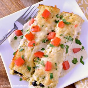 Easy Vegetarian Breakfast Enchiladas recipe ... the perfect meal for breakfast, lunch, or dinner! This delicious Mexican breakfast casserole is packed with yummy ingredients: eggs, black beans, potatoes, and green chiles, wrapped in corn tortillas and baked in a creamy green sauce. So delicious and perfect for a crowd or brunch! | Hello Little Home