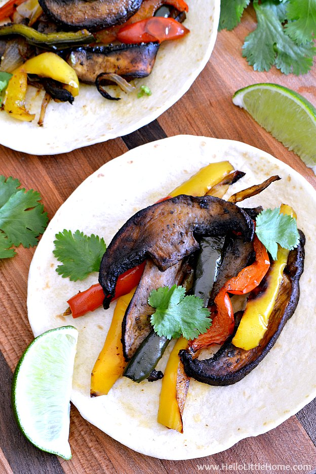 Easy Roasted Veggie Fajitas recipe … a delicious vegetarian Mexican recipe that's perfect for game day meal or a meatless dinner! This vegan veggie fajitas recipe features a tasty mix of roasted vegetables – bell peppers, poblanos, portabella mushrooms, and onions – baked in a yummy seasoning and served with homemade guacamole, sour cream, limes, and cilantro. A healthy vegetable fajitas recipe that can easily be made gluten free! | Hello Little Home