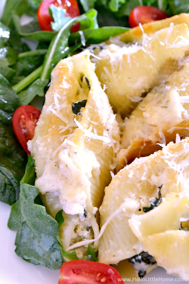 Close up of Spinach and Artichoke Stuffed Shells served with a salad.