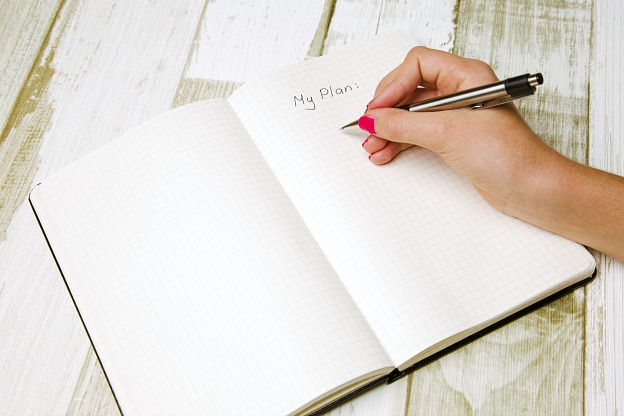 A hand writing in a journal.