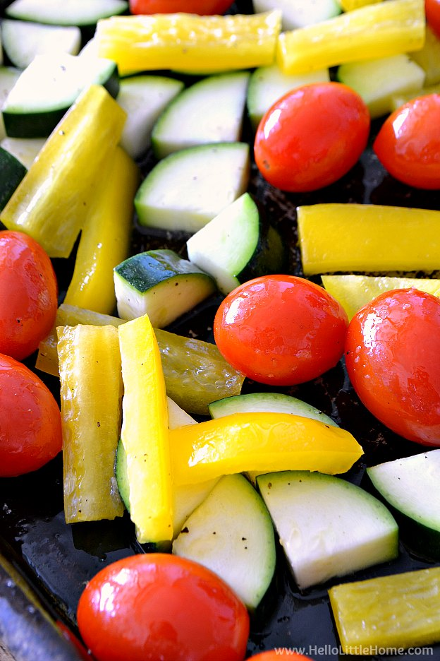 Grape tomatoes, yellow peppers, and zucchini tossed with olive oil on a baking tray.