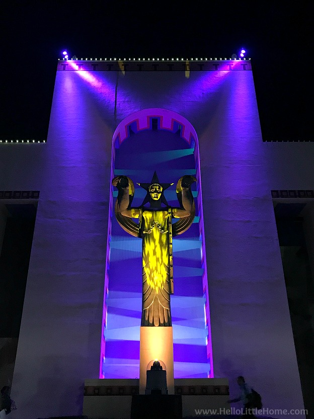 Art deco building and statue in Fair Park lit up at night.