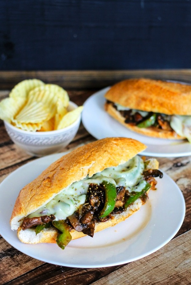 Two Portobello Philly Cheese Steaks served on white plates on a wood table.