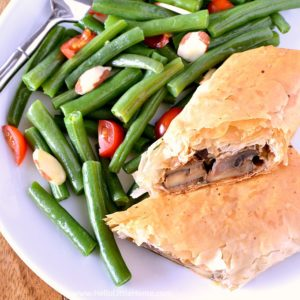 Mushroom Strudel cut in half on a plate with green beans. | Hello Little Home