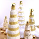 Five Mini Christmas Trees decorated with cream and gold trims and ribbons.