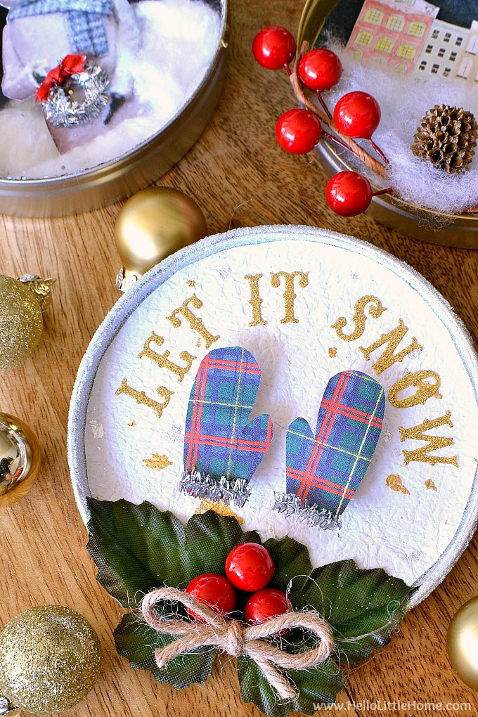 DIY vintage shadow box ornament with mittens, holly, ribbon, and let it snow message.