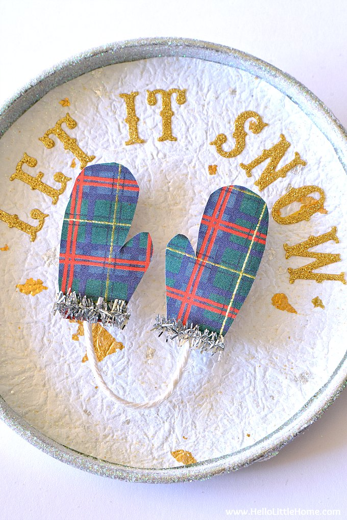 A tin decorated with glitter, paper, mittens, and letters.